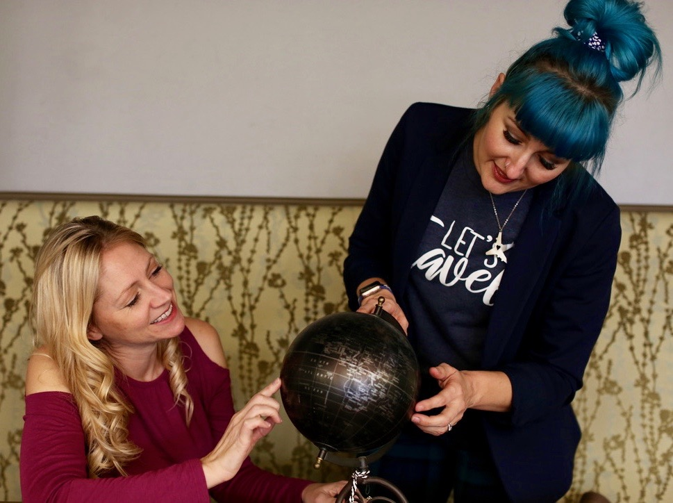 Julie and Katie looking at a globe