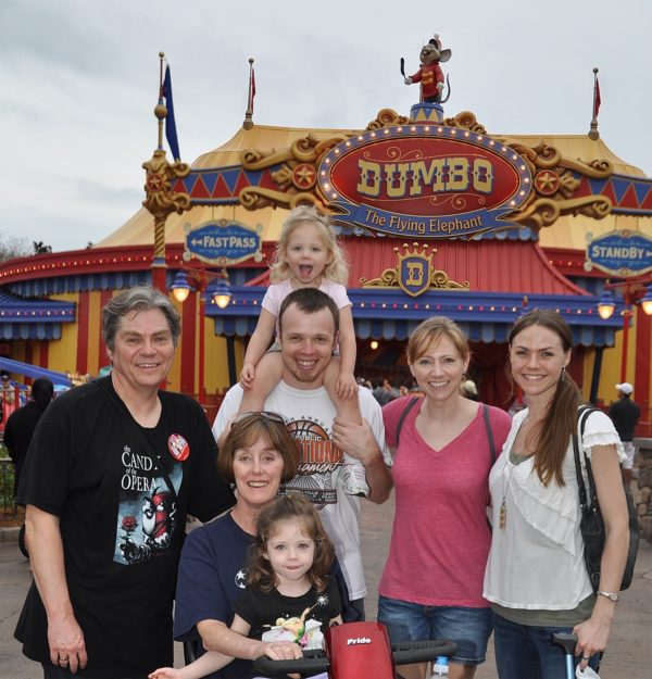 Julie with her parents, sister, husband, and daughters at Disney Land