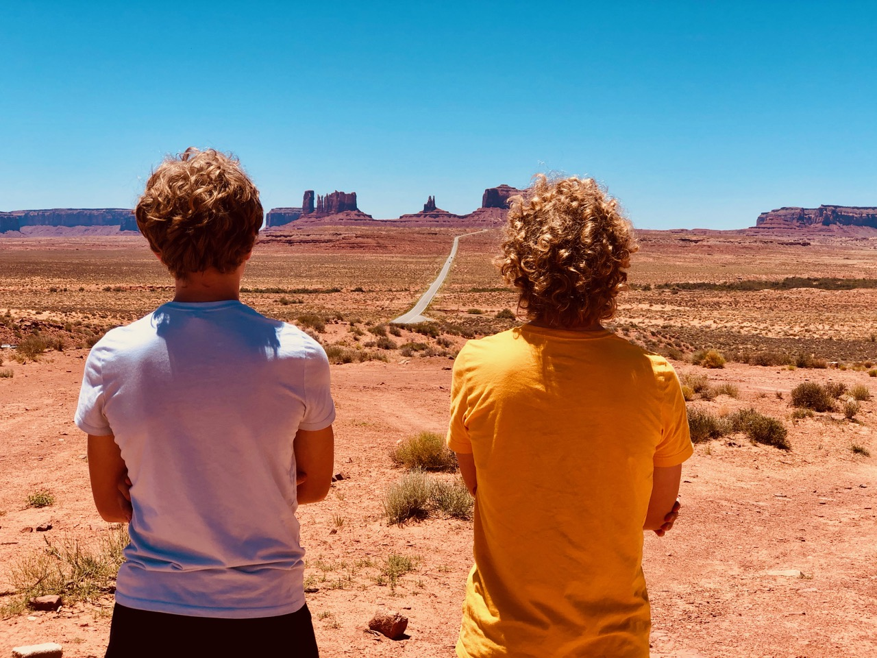 Two boys facing away from the camera, at Monument Valley, Utah