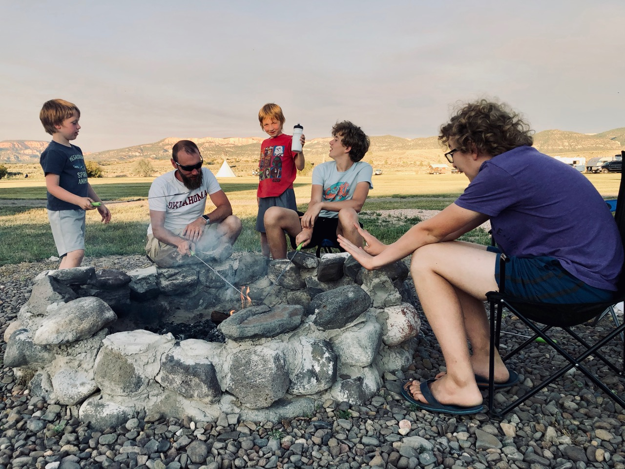 a dad with four boys around a campfire in Utah