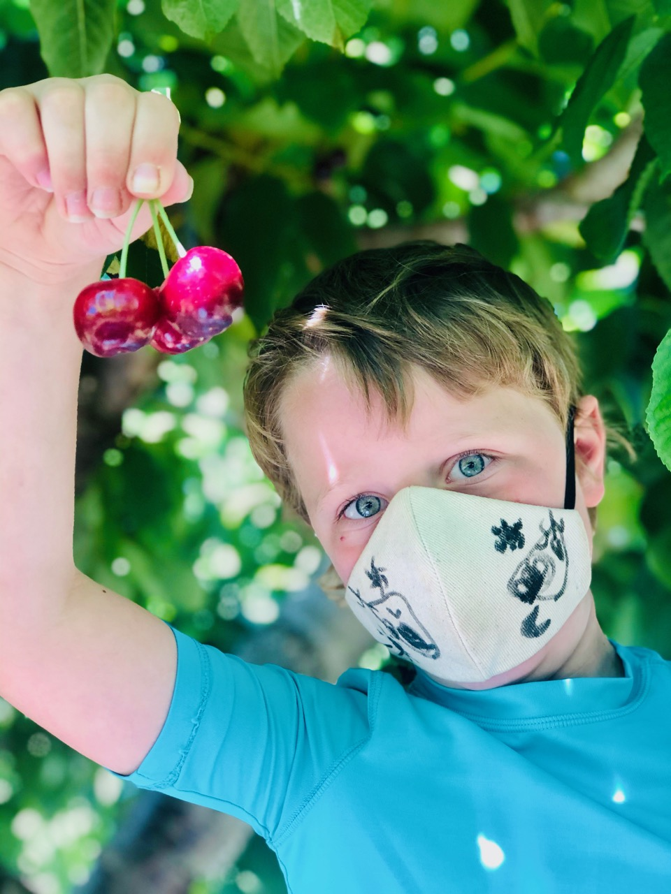 boy with two cherries and a COVID mask.
