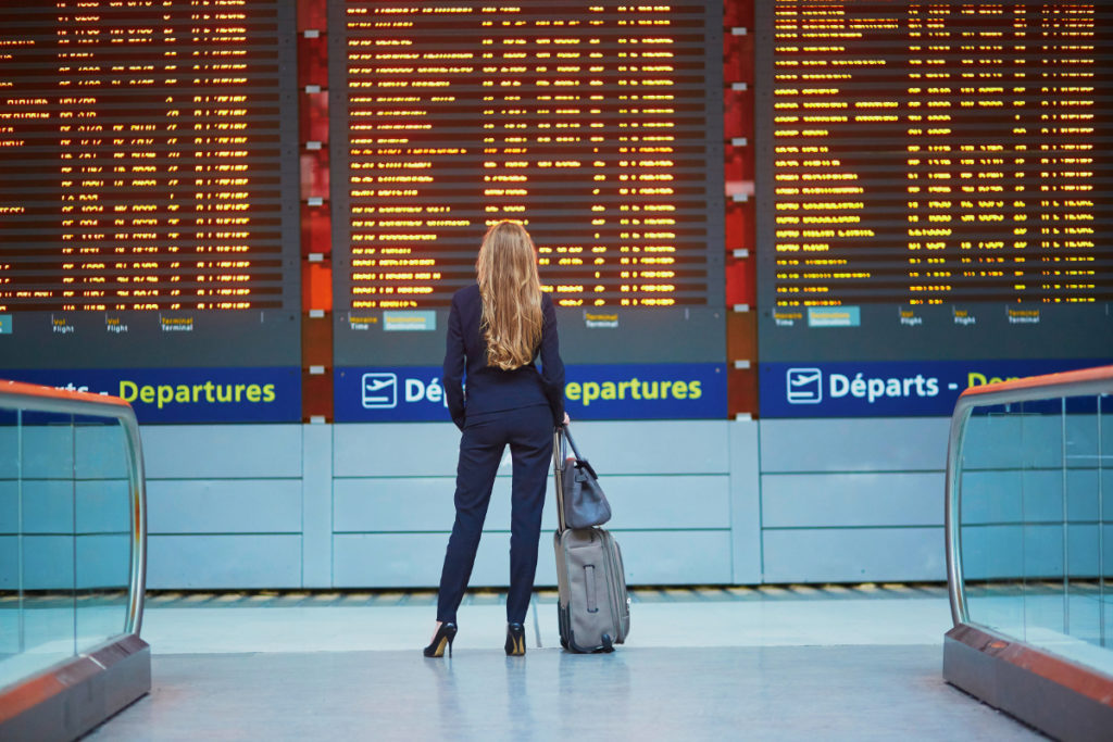 Woman standing at departures board